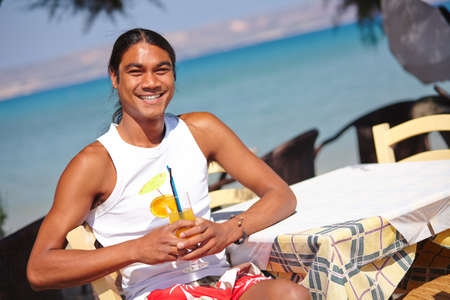 philippine adult: Young Latino man having a drink in summer cafe