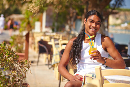 philippine adult: Young Latino man with glass of fresh fruit juice