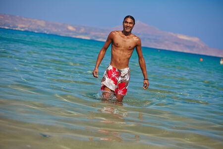 philippine adult: Young shirtless man standing in water