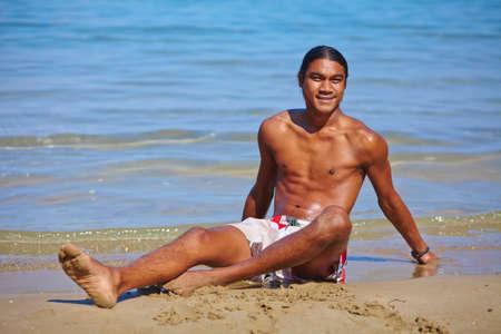 philippine adult: Serene guy resting on sandy seashore