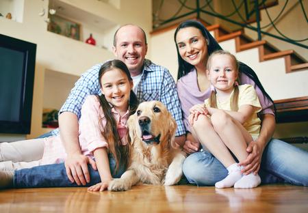 Glückliche Familie von vier und ihren Hund auf dem Boden sitzen zu Hause Standard-Bild - 34897080