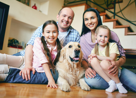 Happy family of four and their dog resting at home on weekend photo