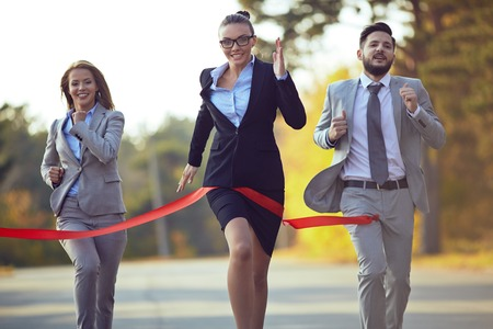 competitive business: Competitive businesswoman coming to finish first with her colleagues behind