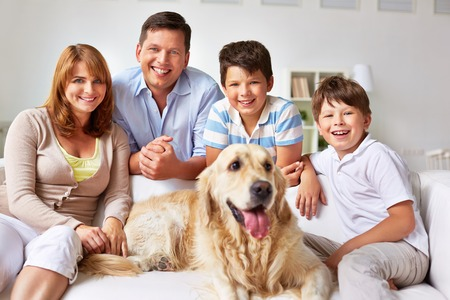 Cute boys, their parents and dog resting on sofa at home photo