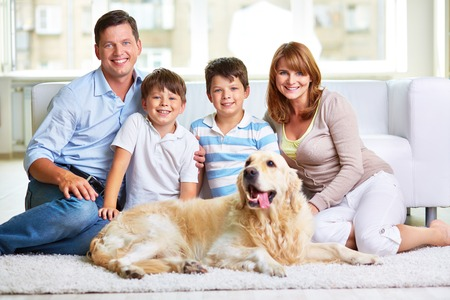 Affectionate couple, their kids and pet spending weekend at home photo
