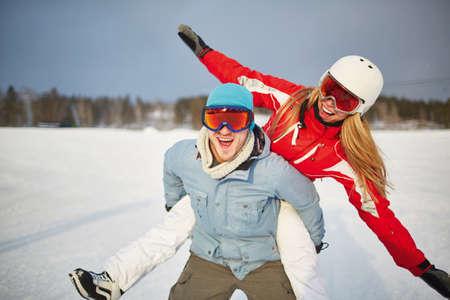 ropa deportiva: Pareja feliz en ropa de deportes de invierno que se divierten al aire libre