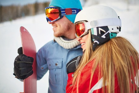 activewear: Young female and male snowboarders in winter activewear Stock Photo