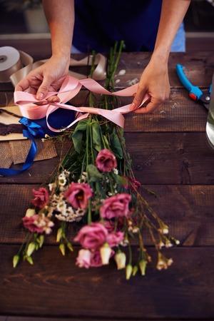 arranging: Florist decorating rose bouquet with ribbon Stock Photo