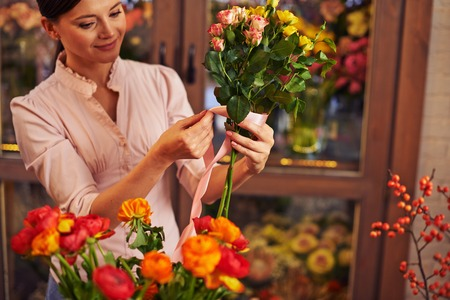 arranging: Young woman working at flower shop Stock Photo