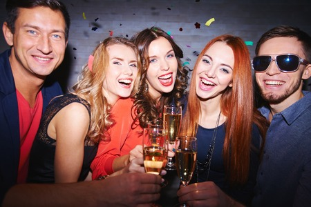 Extatische vrienden met champagne die partij hebben