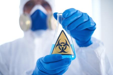 gloved: Close-up of flask with blue biohazard liquid in scientist gloved hands