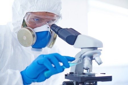 gloved: Gloved scientist studying new chemical substance in microscope