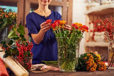 arranging: Flower seller putting flowers into a vase