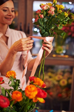 banding: Young woman banding rose bouquet with a ribbon