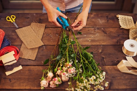 arranging: Florist trimming flowers with pruner