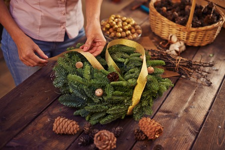 the wreath: Woman decorating coniferous wreath