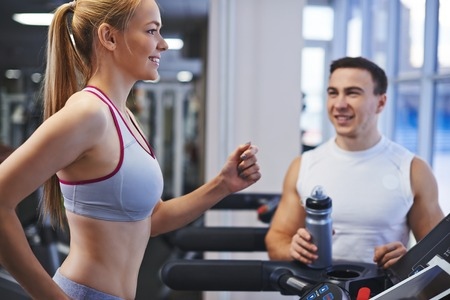sporting activity: Portrait of pretty girl training in gym with her trainer near by