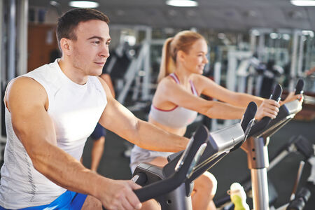 energetic people: Portrait of young man and woman during workout in gym
