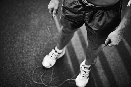 Lower part young man holding skipping rope Reklamní fotografie