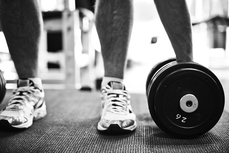 Feet of young man in sneakers taking barbell from the floor