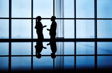 personas comunicandose: Dos personas que se comunican en la oficina oscura Foto de archivo
