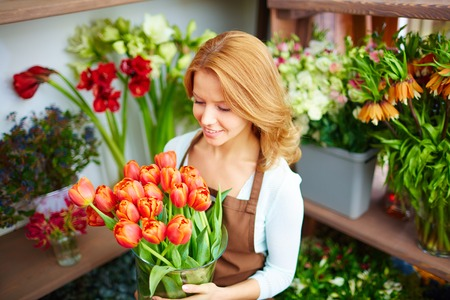Young florist carrying vase of red tulips photo