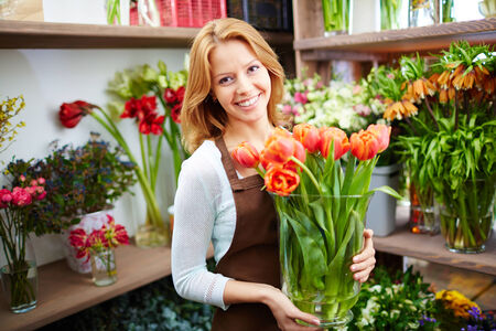 florist shop: Young florist with fresh red tulips in the shop