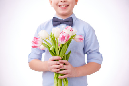 holding mother's hand: Close-up of cut tulips in hands of a child Stock Photo