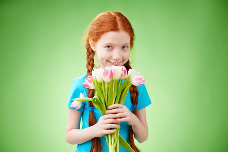 Pretty little girl with bunch of tulips