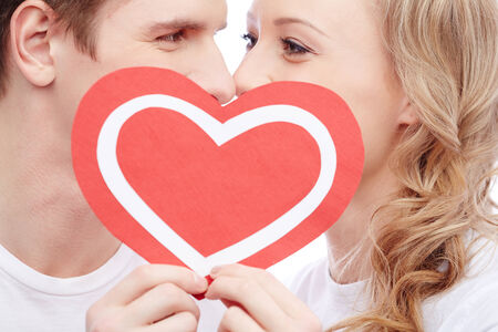 Young people kissing behind paper heart photo