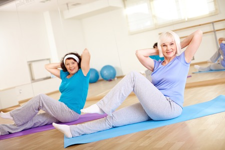 Portrait of sporty females doing physical exercise in sport gym photo