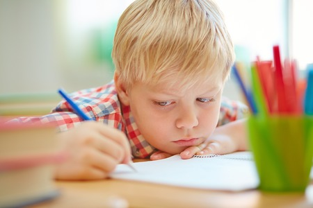 niños escribiendo: Alumno serio que hace notas o dibujar en el libro de ejercicio