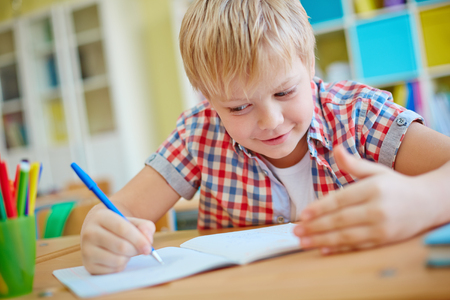 dishonest: Dishonest schoolboy looking at crib on his palm while writing test Stock Photo