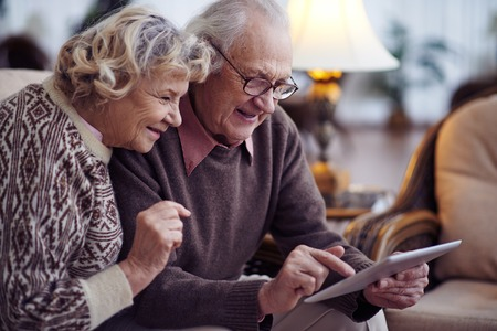 Elderly husband and wife networking at home Stockfoto