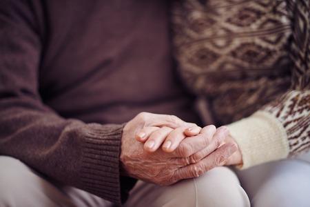Hands of devoted seniors