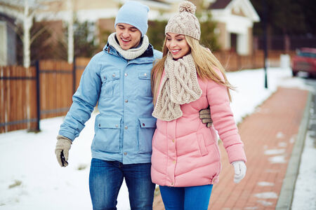 winter couple: Young dates chatting while walking along urban houses in winter