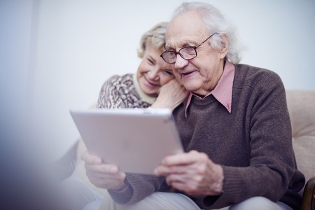husband: Elderly husband and wife using touchpad