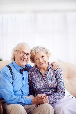 elegantly: Elegantly dressed retired couple looking at camera