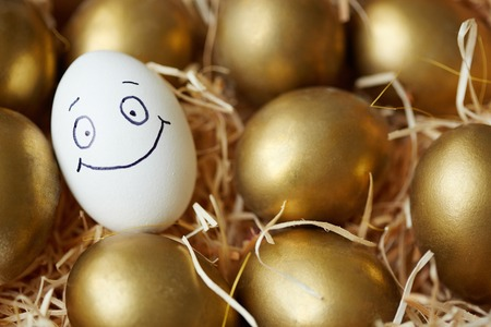 Easter egg with smiley face among golden ones Stock fotó