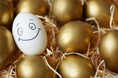 Huevo de Pascua con cara sonriente entre los dorados Foto de archivo - 35794558
