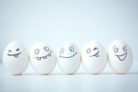 Linie der Eier mit verschiedenen Gesichtsausdrücken Standard-Bild
