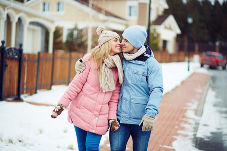 sweethearts: Young sweethearts walking along urban houses in winter