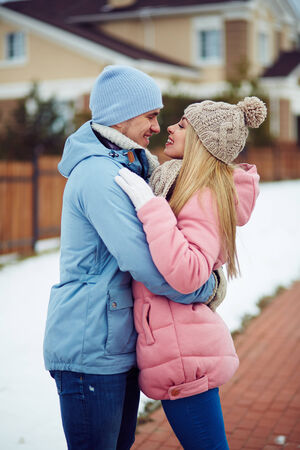 amorous woman: Young dates in winterwear looking at one another in urban environment