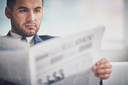 read: A young serious businessman reading newspaper