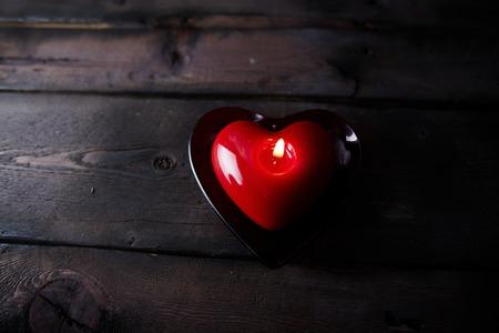bougie coeur: En forme de coeur rouge combustion bougie sur fond de bois