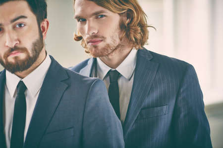 Serious young businessmen in formalwear looking at camera Stock Photo