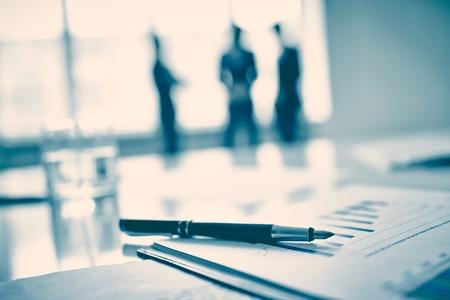 revisando documentos: Pluma en el documento de negocios, tres hombres de pie en el fondo