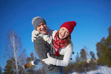 winter couple: Joyful couple in knitted winterwear having fun outdoors Stock Photo