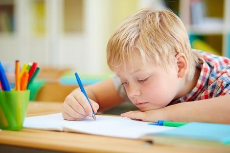 niños escribiendo: Alumno Juvenil haciendo notas o dibujar con la pluma en la lección