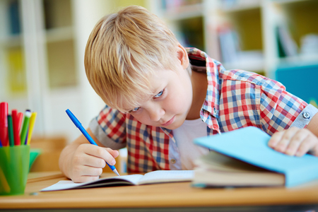 dishonest: Dishonest schoolboy looking the right answer in book during test